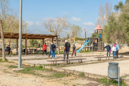 Vilafranca de Bonany, Spain, February 27 2021: group of elderly people playing a game of petanque in a public park. Everyone wears face masks because of the pandemic. New normal concept Editöryel