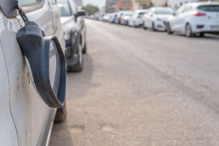 Close-up of a broken rearview mirror of a white automobile on an out of focus city street