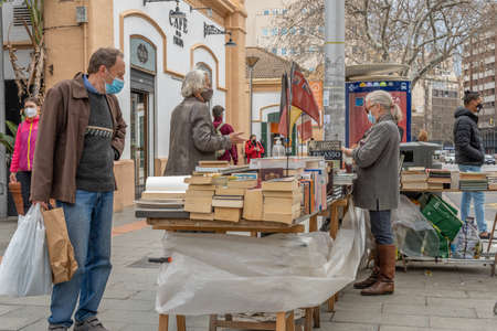 Palma de Mallorca, Spain; March 04 2021: Street stall selling second-hand-books. The sellers and buyers wearing face masks and keeping a safe distance due to the Coronavirus pandemic. New normal Editöryel