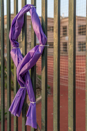 Symbol of a purple ribbon made of fabric and tied with flanges to a metal gate of a closed and unfocused educational center. Symbol commemorating International Women's Day, March 8