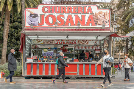 Palma de Mallorca, Spain: March 04 2021: Plaza de Espana in the city of Palma de Mallorca post-pandemic. Churreria Josana street food stall with pedestrians walking with face mask Editöryel