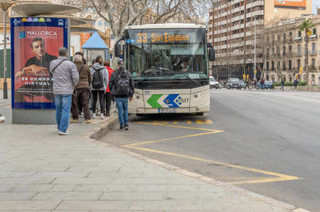 Palma de Mallorca, Spain; March 04 2021: EMT bus picking up passengers at a bus stop in Plaza España in Palma de Mallorca. Passengers and driver with face masks. New normal concept