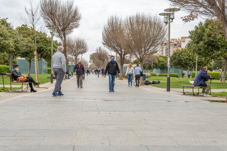 Palma de Mallorca, Spain; March 04 2021: People wearing face masks strolling through the Parque de las Estaciones in the historic center of Palma de Mallorca. New normality
