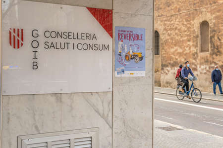 Palma de Mallorca, Spain; March 04 2021: Main entrance of the Council of Health and Consumption written in Catalan language. In the background pedestrians and urban cyclists wearing facial mask Editöryel