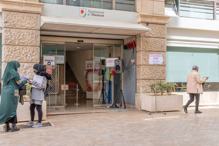 Manacor, Spain; March 18 2021: Main entrance of the Manacor City Hall with people waiting their turn outside and wearing face masks because of the Coronavirus pandemic. New normal concept Editöryel
