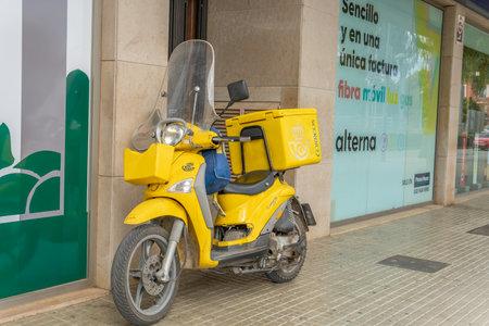 Manacor, Spain; March 18 2021: General view of a motorcycle of the company Sociedad Estatal de Correos y Telegrafos de España (Correos) in the Majorcan town of Manacor Editöryel