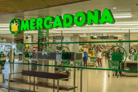 Manacor, Spain; March 18 2021: entrance of a supermarket of a Spanish food chain (Mercadona). Inside there are customers shopping and wearing face masks due to the Coronavirus pandemic. New normal Editöryel