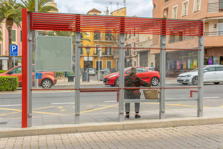 Manacor, Spain; March 18 2021: Elderly person with a wicker basket waiting for the bus sitting with her back to a bus shelter in a central street of the Mallorcan town of Manacor Editöryel