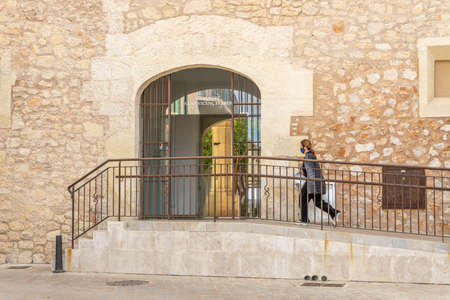 Manacor, Spain; March 18 2021: Entrance to the Cloister of Sant Vicenç Ferrer, historic building that houses the municipal library of Manacor. A person wearing a facial mask walking. New normal Editöryel
