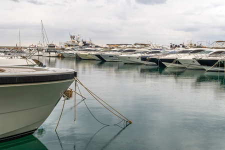 Luxury yachts moored in a marina of the island of Mallorca on a cloudy rainy day Stok Fotoğraf