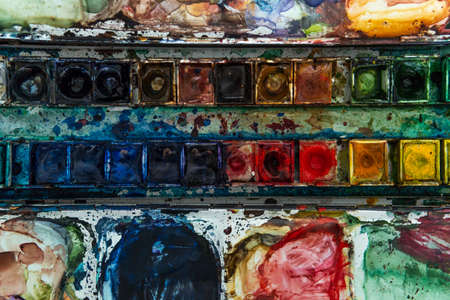 Close-up of a watercolor palette with different colors with a hand drawing in the background out of focus Stok Fotoğraf