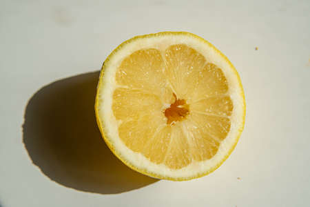 Close-up of a halved lemon in direct sunlight casting a strong shadow on a neutral background