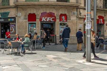 Palma de Mallorca, Spain; April 23 2021: Main facade of the franchise restaurant Kentucky Fried Chiken KFC in Plaza de España. Citizens wearing face masks due to the Coronavirus pandemic. New normal