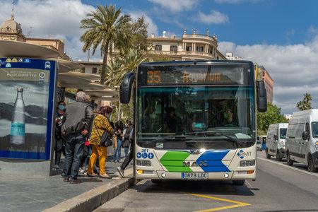 Palma de Mallorca, Spain; April 23 2021: Bus stop at Plaza de España in Palma de Mallorca. Passengers and driver wearing facial surgical masks due to the Coronavirus Pandemic. New normality concept Editorial