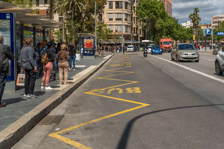 Palma de Mallorca, Spain; April 23 2021: Bus stop at Plaza de España in Palma de Mallorca. Passengers waiting with wearing facial surgical masks due to the Coronavirus Pandemic. New normality concept