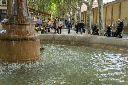 Palma de Mallorca, Spain; April 23 2021: Close-up of the stone fountain in the historic center of Palma de Mallorca with people out of focus in the background Editorial
