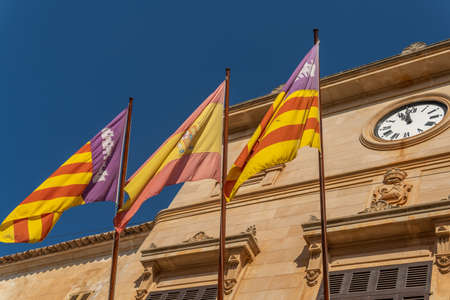 Main facade of Santanyi Town Hall with the flags of Spain, the Balearic Islands and Mallorca. Island of Mallorca, Spain Stock Photo