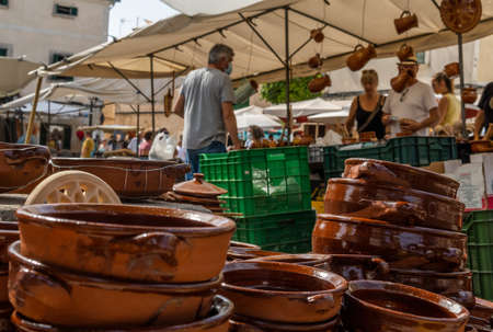 Close-up of popular ceramic kitchen utensils from the island of Mallorca at a street market. In the background unrecognizable people selling and buying ceramic handicraft products Stock Photo