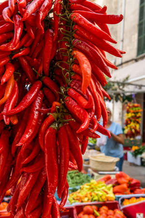 Close-up of a bunch of red peppers typical of the island of Mallorca at a street market selling fresh produce