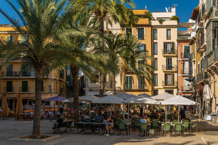 Palma de Mallorca, Spain; September 10 2021: Plaza de la Lonja in the historical center of Palma de Mallorca at sunset in summer. Tourists having a drink in the terraces of the cafes