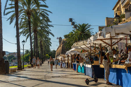 Palma de Mallorca, Spain; September 10 2021: Tourist market selling handicrafts on the promenade in the city of Palma de Mallorca with people browsing and shopping at the stalls at sunset