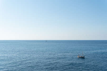 General view of the Mediterranean Sea with a fishing boat, called Llaut, sailing in the sea. Rocky coast of the island of Mallorca, Spain