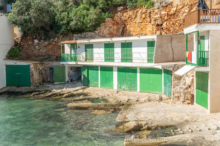 Traditional white jetties on the island of Mallorca with green doors at sunrise in summertime