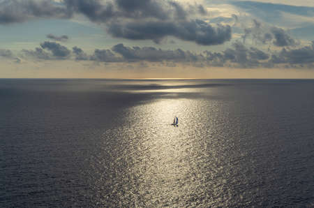 Seascape of the Mediterranean Sea at sunset with clouds and a ship sailing in its waters. Sublime landscape of a sunset from the island of Mallorca, Spain