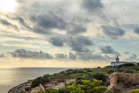 Cap Blanc lighthouse on the rocky coast of the island of Mallorca. In the background s seascape of the Mediterranean Sea at sunset with clouds. Sublime landscape Stock Photo