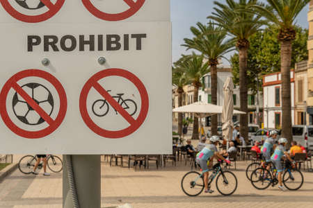 Close-up of a sign written in Catalan language prohibiting playing ball and riding bicycles in a public park. In the background, out of focus people riding bicycles. Non-citizenship conceptual image Stock Photo