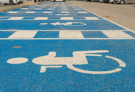 Parking area for disabled people painted in blue and with the symbol of disabled people in white. Image of accessibility for disabled people