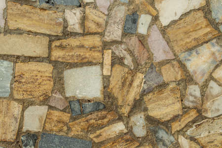 Texture image of a white, blue and yellow colored stone wall with cement. Background image Stock Photo