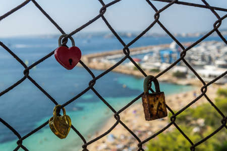 Close-up of padlocks on a metal fence with the background of the island of Mallorca out of focus