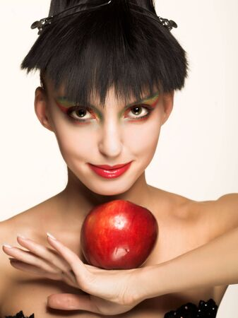 Portrait of young brunette with red apple photo