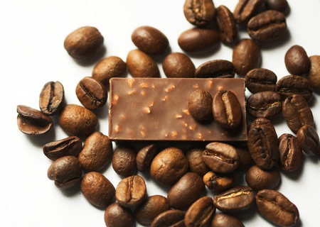 caf: Coffe and pieces of milk chocolade on light background.