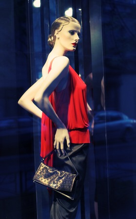 Photo of modern clothing shop window with mannequin photo