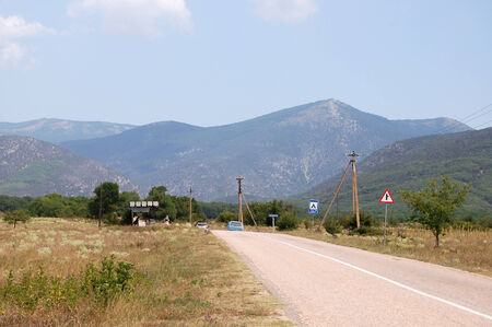 midday: Country road in Crimea at sunny summer midday