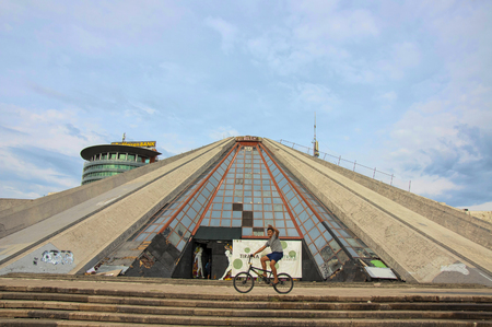 Tirana, Albania - 16 July 2017 : Albanian boy riding a bike in front of The Pyramid of Tyrana - peculiar architectural structure in the centre of the city. Since its opening in 1988 Pyramid perfomed function of Enver Hoxha museum, conference center, exhi Редакционное