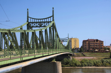Trajan bridge crossing Mures river in Arad, Romania at sunny summer day