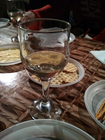 The glass with a little of white wine staying on the table covered with oil cloth  among different snacks