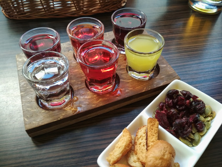 The set of six shot glasses with multicolored liqueurs on the tray and  different snacks in saucer laying on the table Фото со стока