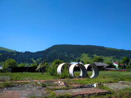 Three concrete rings lieing on mountain countryside