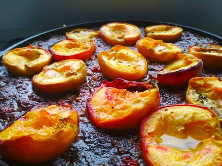 Stew with baked peaches, shugar and spice on the pan close up