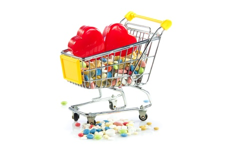 shopping trolley with pills,heart  isolated on white background photo
