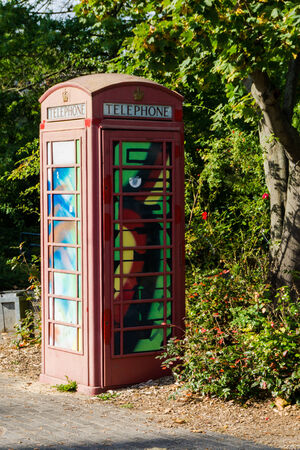 social history: painted old red phone booth, phone box, painted in different colors, london