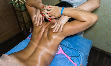 humane: masseur doing massage on woman body in the spa salon. spa treatment, health spa, massaging.
