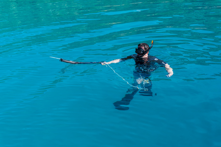 spearfishing: underwater hunter with a gun in a mask. speargun