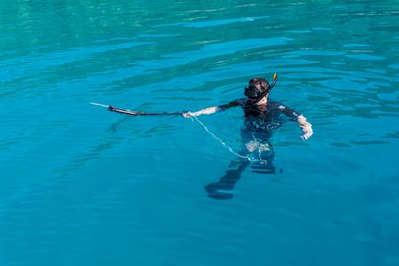 underwater hunter with a gun in a mask. speargun