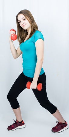 lift hands: girl with dumpbells on white background sport concept gym Stock Photo