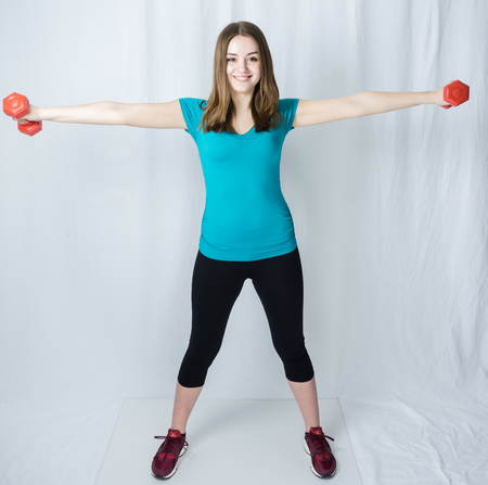 girl with dumpbells on white background sport concept gym Stock Photo